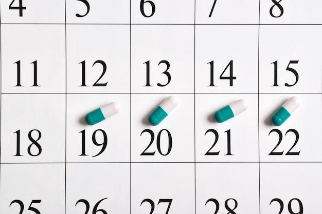 Medicinali. un primo piano delle capsule verdi con le pillole è nel calendario. un piano farmacologico, un programma, un elenco o un concetto di calendario.