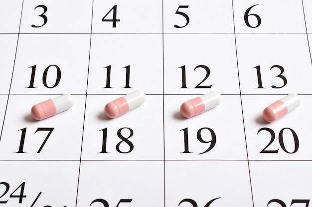 Medicinali. un primo piano di capsule rosa con pillole è nel calendario.