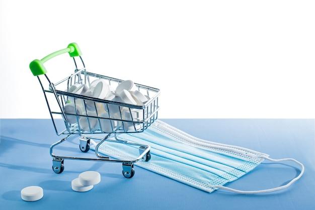 Medicinali nel carrello del piccolo supermercato e maschere mediche
