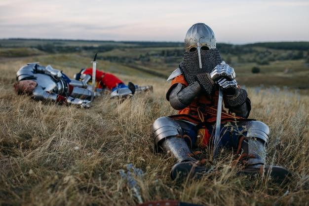Cavaliere medievale in armatura e casco seduto a terra dopo una grande battaglia. antico guerriero corazzato in armatura in posa sul campo