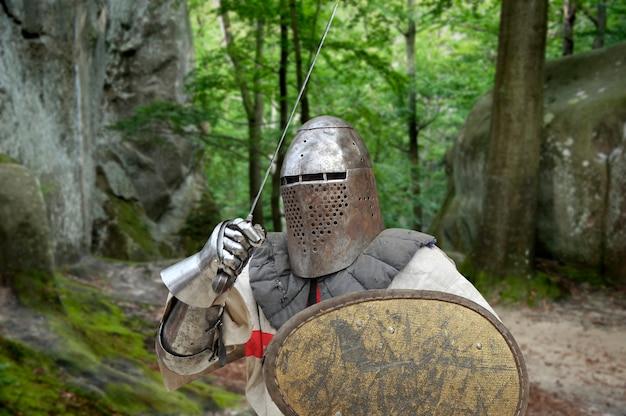 Cavaliere medievale con spada e scudo in una fitta foresta