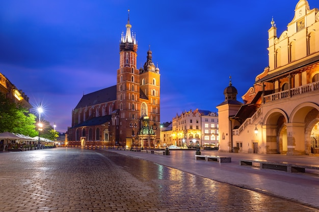 Piazza del mercato principale medievale con la basilica di santa maria nel centro storico di cracovia all'alba