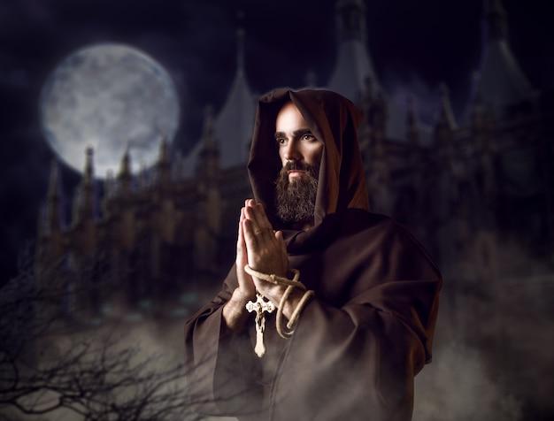Monaco medievale in veste nera con cappuccio che prega contro il castello e la luna piena nella notte, rituale segreto. frate misterioso in mantello scuro. mistero e spiritualità