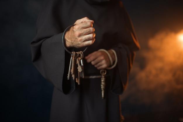 Monaco medievale tiene in mano un mazzo di chiavi