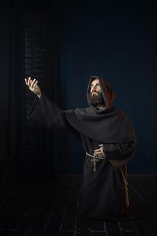 Monaco medievale in ginocchio e in preghiera, religione. frate misterioso in mantello scuro, mistero e spiritualità