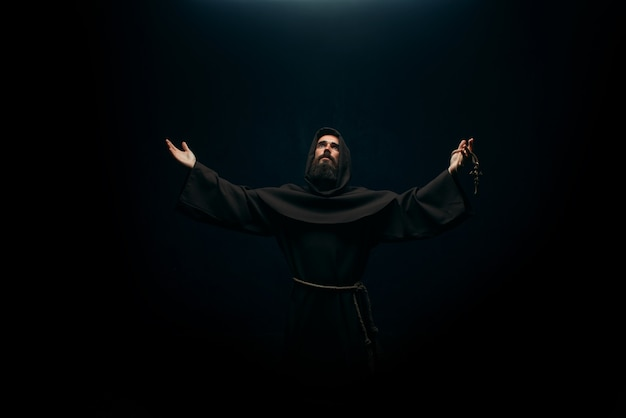 Monaco medievale che prega al dio santo, religione. frate misterioso in mantello scuro, mistero e spiritualità