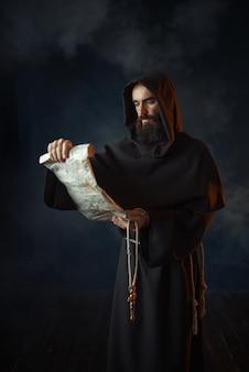 Monaco medievale legge una preghiera nell'antico manoscritto, la religione. frate misterioso in mantello scuro. mistero e spiritualità