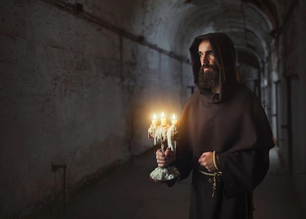 Monaco medievale in veste tiene in mano un candelabro