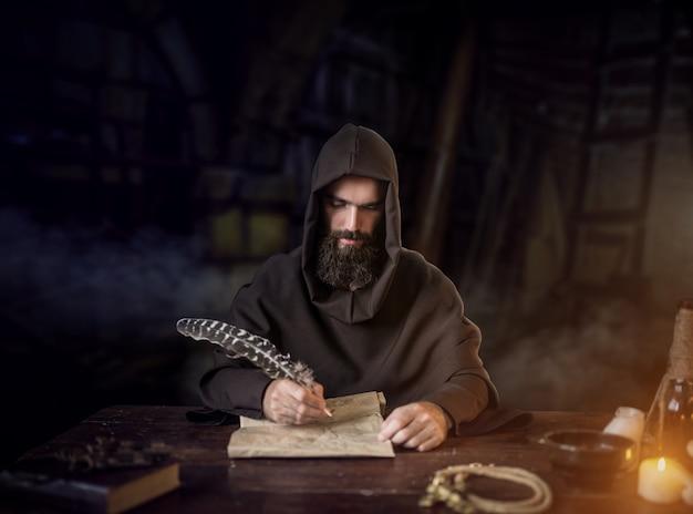Il monaco medievale in veste scrive con una piuma d'oca