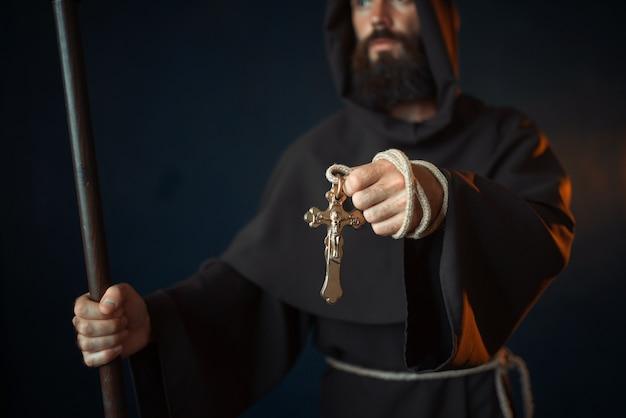 Monaco medievale con bastone di legno e croce in mano, religione. frate misterioso in mantello scuro, mistero e spiritualità