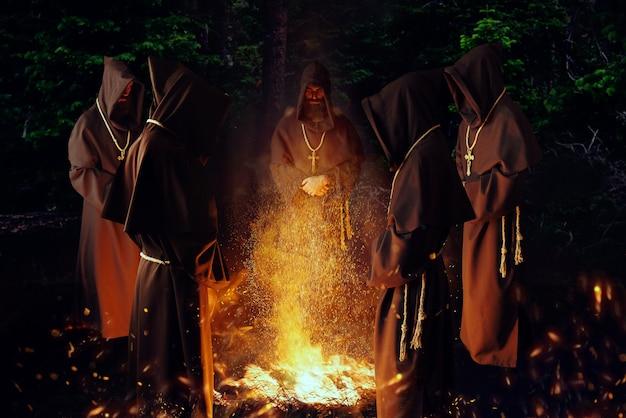 Monaci medievali che pregano contro un grande fuoco nella notte, rituale segreto. frate misterioso in mantello scuro. mistero e spiritualità
