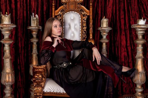 Regina medievale in abiti storici sul trono d'oro nel castello. ritratto di giovane donna in un abito vecchio stile su un trono antico nella sala di ricevimento della fortezza. concetto di eventi in costume a tema