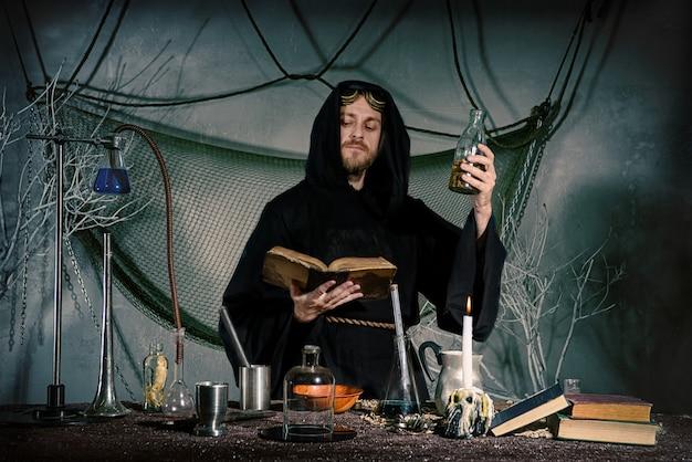 Lo scienziato medievale scienziato medievale nel suo laboratorio legge un incantesimo.