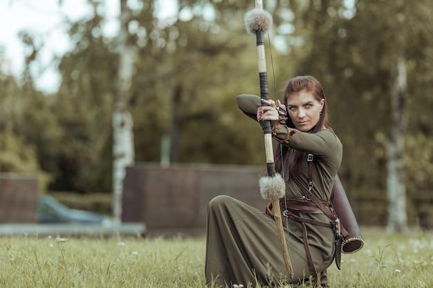 La guerriera medievale con un arco siede in una radura e mira da un arco, cacciando in una foresta verde
