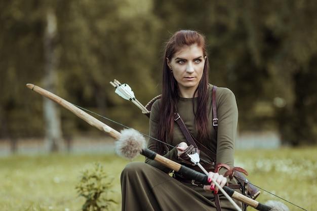 La guerriera medievale con un arco siede in una radura, a caccia in una foresta verde