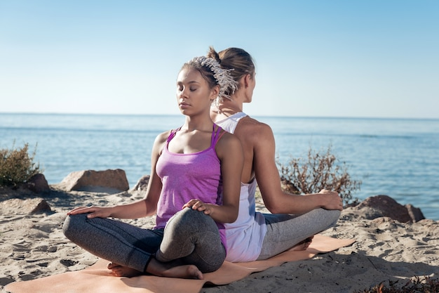 Medita con il tuo ragazzo. bella donna sottile con i dreadlocks meditando insieme al suo fidanzato vicino al fiume