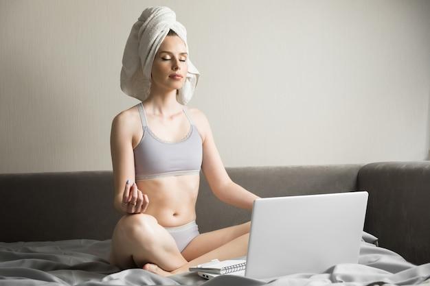 Meditando con il laptop, allevia le emozioni negative durante il fine settimana a casa, la giovane imprenditrice pacifica consapevole o lo studente che praticano esercizi di yoga respirazione sul posto di lavoro