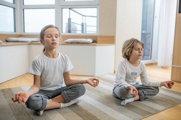 Meditazione. bambini che fanno yoga insieme a casa e si siedono in meditazione