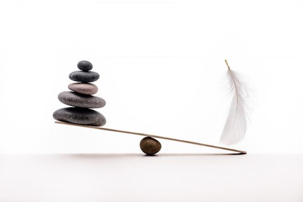 Pietre e piuma di meditazione isolate su fondo bianco. concetto di pesante e leggero.