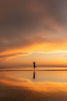 Posa di yoga dell'albero di pratica della donna di meditazione sulla spiaggia al tramonto