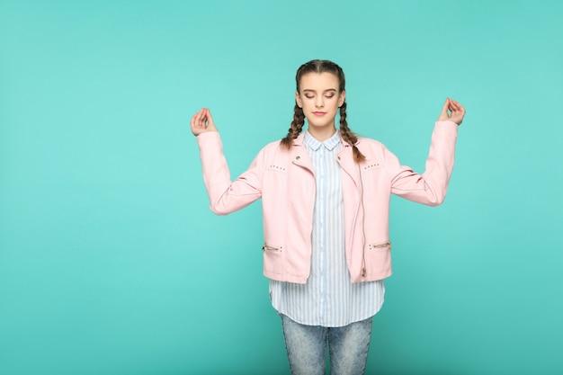 Meditazione e yoga ritratto di bella ragazza carina in piedi con trucco e acconciatura codino marrone in giacca rosa camicia a righe azzurre. indoor, studio shot isolato su sfondo blu o verde.