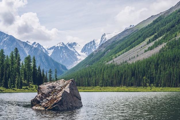 Vista meditativa al bellissimo lago con pietra nella valle su sfondo di montagne innevate.