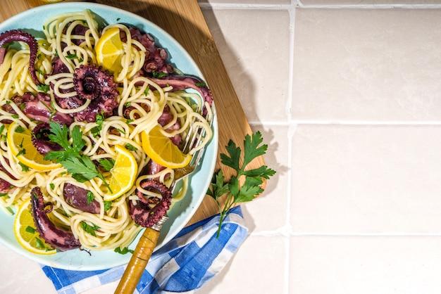 Cibo mediterraneo, pasta di polpo fatta in casa con limone ed erbe aromatiche, su piastrelle estive sfondo soleggiato vista dall'alto spazio copia