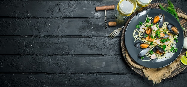 Cucina mediterranea. spaghetti ai frutti di mare con vongole e vino bianco sulla tavola di legno nero