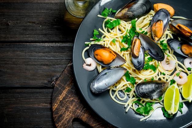 Cucina mediterranea. spaghetti ai frutti di mare con vongole e vino bianco sulla tavola di legno.