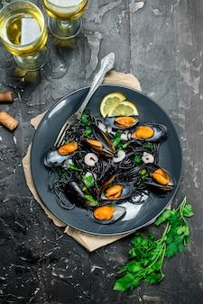 Cucina mediterranea. spaghetti al nero di seppia, vongole e vino bianco su tavola rustica nera.