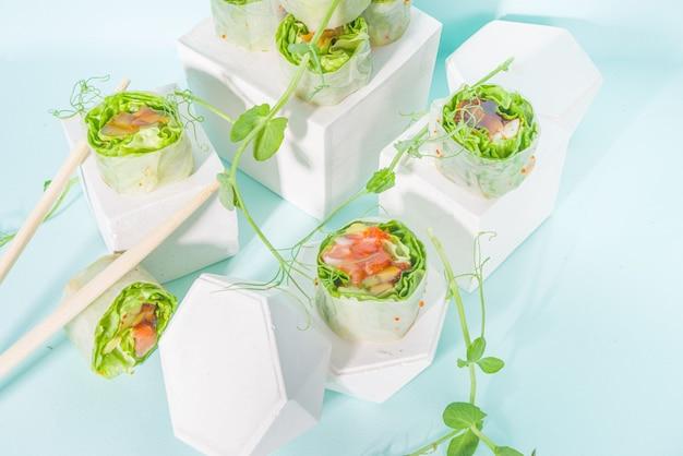 Concetto di dieta mediterranea, nordica e cheto. sushi senza riso, cibo dietetico con frutti di mare, verdure. involtini primavera alla moda in stile sushi asiatico su sfondo blu moderno