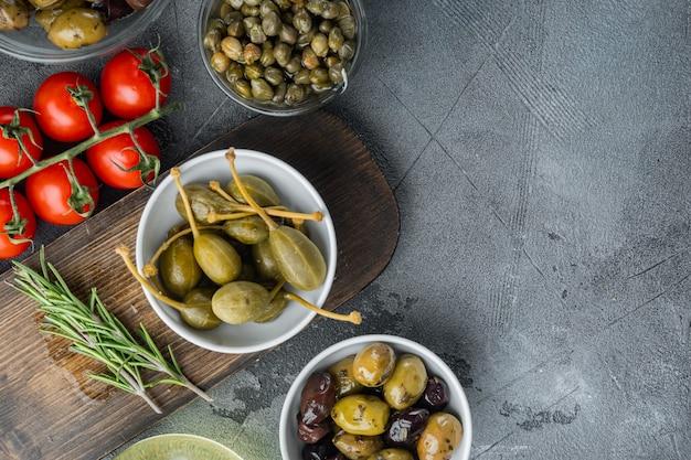 Olive mediterranee e capperi con erbe aromatiche, su sfondo grigio, distese piatte con spazio copia per il testo