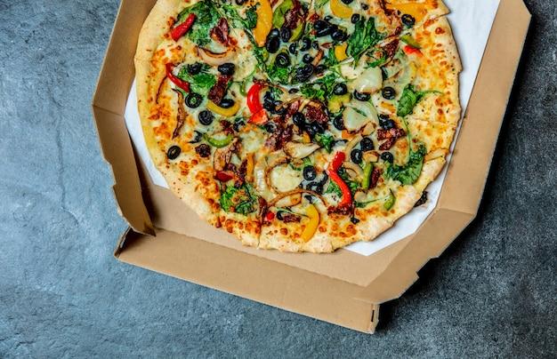 Pizza mediterranea con olive e formaggio in cartone su un tavolo
