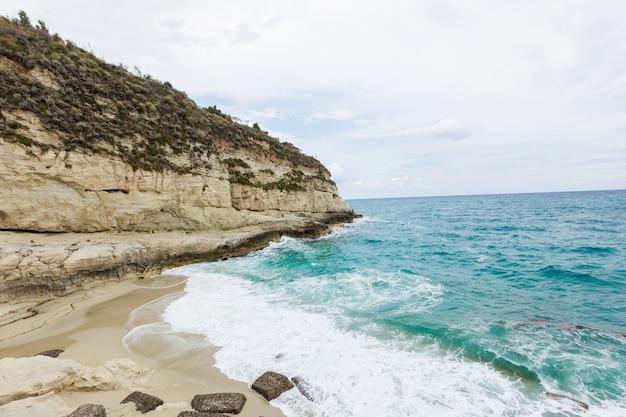 Rocce del mare blu di vista sul mare mediterraneo sulla spiaggia calabrese di giorno di estate della costa vicino a tropea