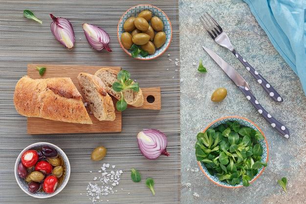 Set di snack mediterranei. olive verdi e nere, pagnotta di pane multicereali fresco, insalata di mais e cipolla rossa su sfondo di legno vecchio. vista dall'alto con spazio per il testo