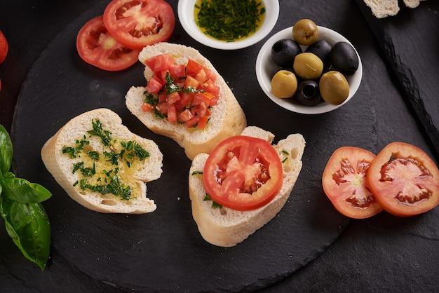 Set di spuntini mediterranei. olive, olio, erbe aromatiche e ciabatta a fette su una tavola di legno sul bordo di pietra ardesia nera su superficie scura, pomodori succosi su pane fresco, pesto come condimento. vista dall'alto. lay piatto