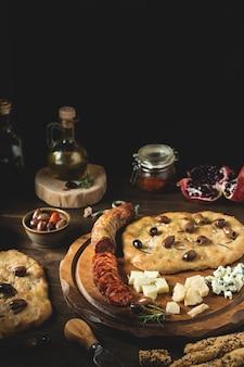 Antipasto in stile mediterraneo con focaccia e olive su fondo rustico in legno scuro