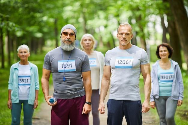 Colpo di ritratto di gruppo medio lungo di partecipanti senior attivi della gara di maratona nel parco forestale che guarda l'obbiettivo