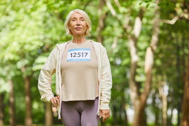 Colpo medio del ritratto di bella donna senior caucasica che prende parte alla maratona di estate che guarda l'obbiettivo, lo spazio della copia