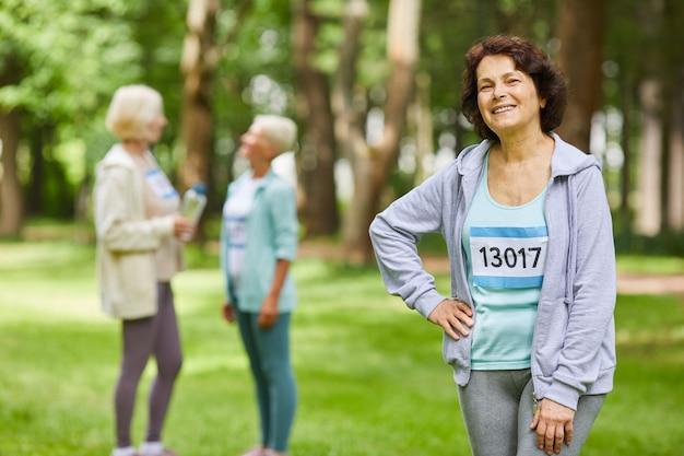 Colpo medio del ritratto dell'anziano allegro con capelli castani che indossa attrezzatura sportiva in piedi nel parco con i suoi amici che chiacchierano dietro che guarda l'obbiettivo