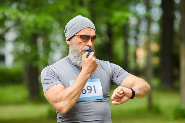 Colpo medio ritratto di allenatore sportivo professionista che inizia l'allenamento per la maratona con il fischio