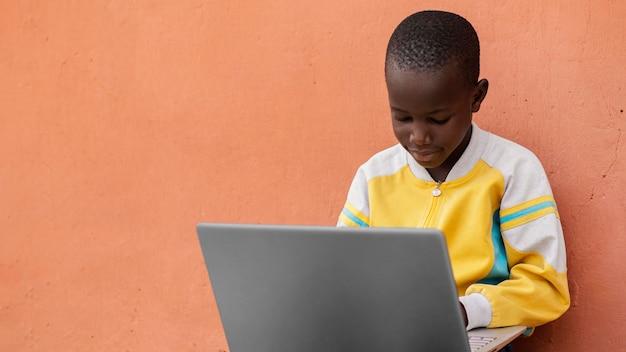 Bambino africano del colpo medio con il computer portatile