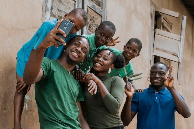 Persone africane di tiro medio che prendono selfie