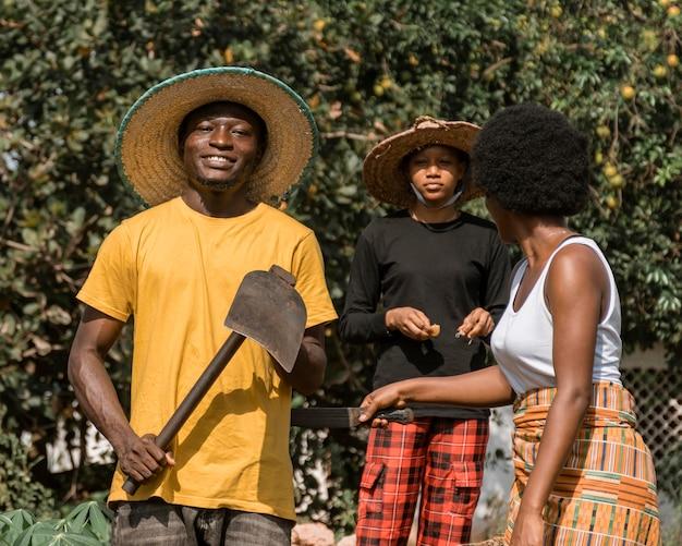 Gente africana di tiro medio con vanga