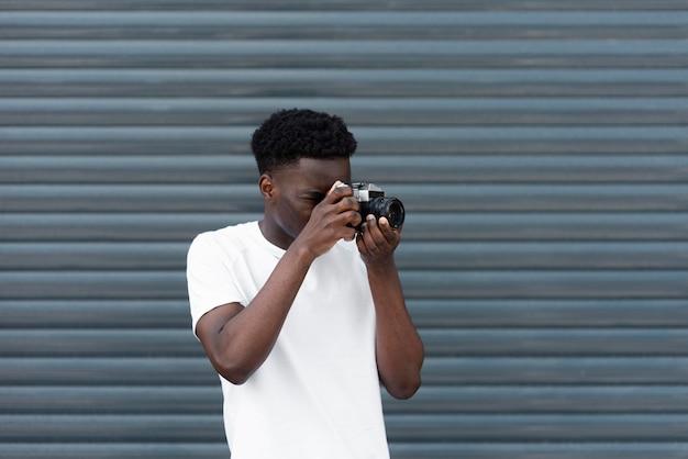 Fotocamera della holding del ragazzo del colpo medio