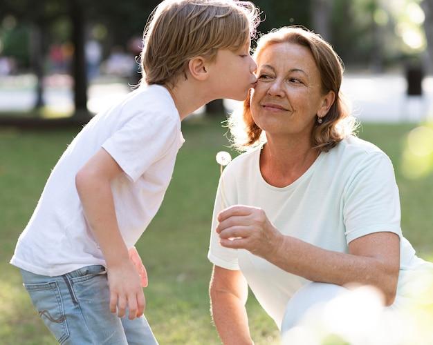 Ragazzo del colpo medio che bacia la nonna