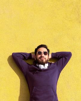 Ragazzo del colpo medio che pone con gli occhiali da sole