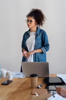 Donna di affari del colpo medio con il computer portatile