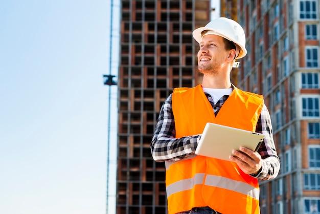 Ingegnere edile di colpo medio facendo uso della compressa