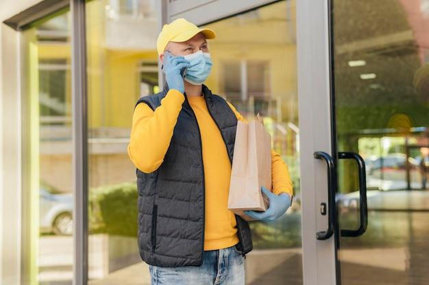 Uomo di consegna del colpo medio che tiene il sacchetto di carta